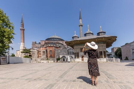 Beautiful girl in the white hat in front of Fountain of Ahmed III near Hagia Sophia at Istanbul Turkey. Reklamní fotografie