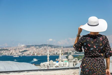 Beautiful girl in the white hat in front of city panorama at Istanbul Turkey. Reklamní fotografie