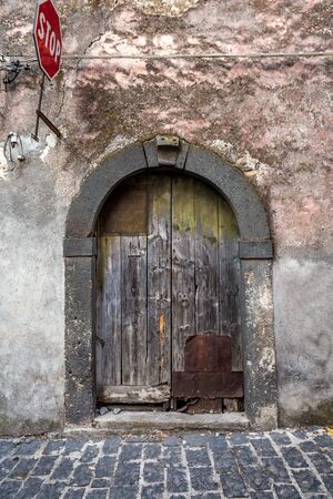 Old wooden entrance door on facade of antique baroque building in traditional architecture of Catania Sicily, Italy.