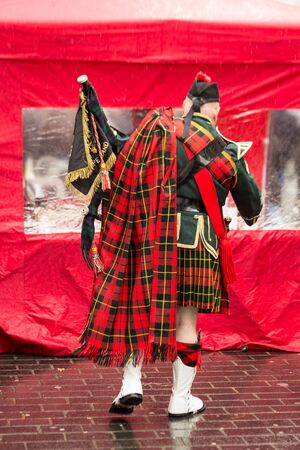 A man dressed in the national costume of Scotland. Mens skirt. On the shoulder of men in a large red checkered scarf. Liverpool. England.