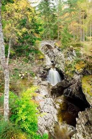 A small natural waterfall in the forest. Through it is made a stone bridge, on which you can cross the water. Autumn day. Scotland.