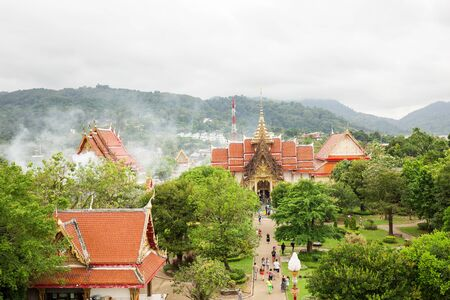 Temples with a red roof. Around the boors is a beautiful garden. Tourists walk in the park. phuket, thailand