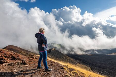 Elderly female traveler admiring breathtaking volcanic landscape of Etna covered with clouds at Catania Sicily, Italy. Stock fotó - 130123074