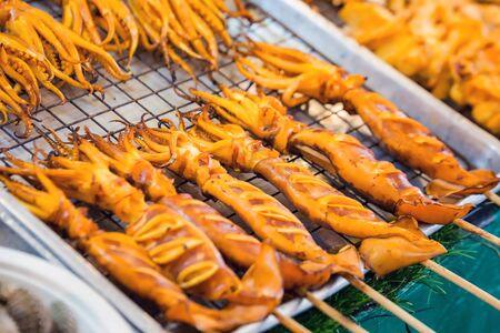 Grilled squid, sold on the market in Bangkok. Thailand street food. Banco de Imagens