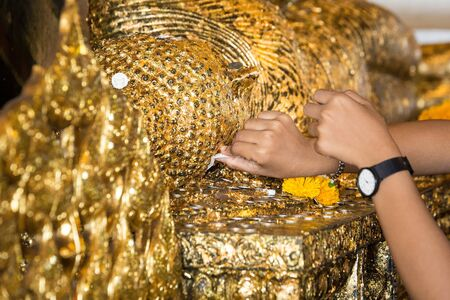 A man touches the temple of the Buddha statue made of gold. Imagens