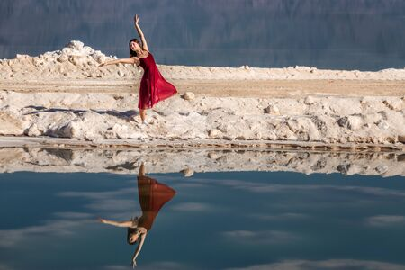 Beautiful girl in a red dress shows dance moves reflected in the still mirrored water of the Dead Sea, Israel.