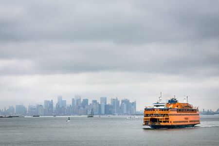 Orange ferry from Staten island to New York city at foggy day.