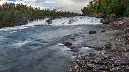 Malselvfossen waterfall in Norway in warm autumn colors and big rainbow.