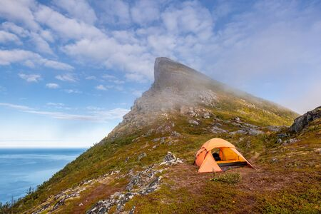 Tent on mountain ridge over clouds adventure journey traveling outdoor in Norway active vacations sunset Segla mountain, Senja.