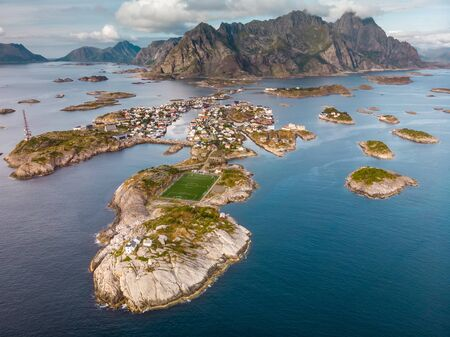 Incredible aerial view of Henningsvaer, its scenic football field and mountains in the background. A small fishing village located on several small islands in the Henningsvaer, Lofoten Islands, Norway Imagens
