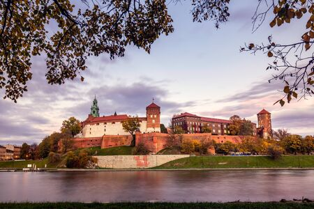 Wawel castle famous landmark in Krakow Poland. Picturesque landscape on coast river Wisla. Autumn sunset with white sky and clouds. Long exposure shot.