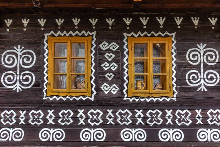 Old wooden houses in Slovakia village Cicmany in autumn. Unique decoration of log houses based on patterns used in traditional embroidery in village of Cicmany Stock Photo