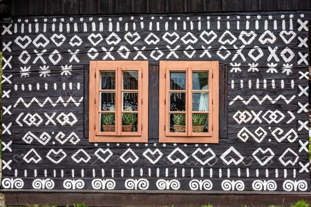 Old wooden houses in Slovakia village Cicmany in autumn. Unique decoration of log houses based on patterns used in traditional embroidery in village of Cicmany