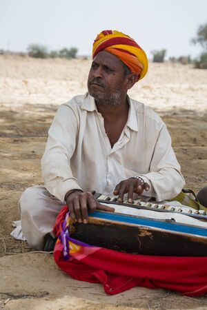 Jaisalmer, India - March 09 2017: A man plays a musical instrument sitting in the shade of a tree in the desert.
