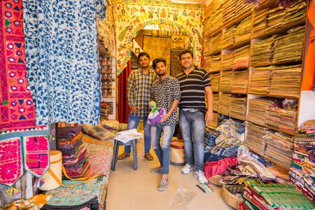 Jodhpur, India - March 07 2017: three men working in a shop selling womens headscarves. They happily welcome customers.