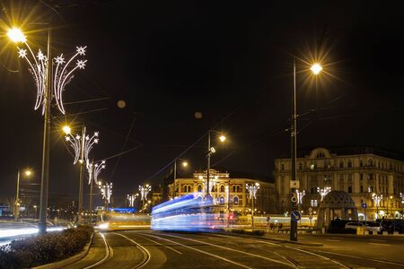 Christmas lights tram rides in Budapest. Long exposure effect. Famous yellow tram going on Holiday Christmas decorated street in Budapest near the Parliament building and chain bridge  in evening.
