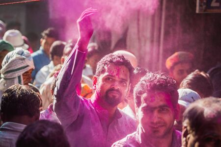 Vrindavan, India - March 12 2017: Indian people covered in different colours celebrating Holi festival in Vrindavan, India.