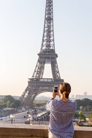 Beautiful girl takes a photo with smartphone of the famous Eiffel Tower in Paris, France.