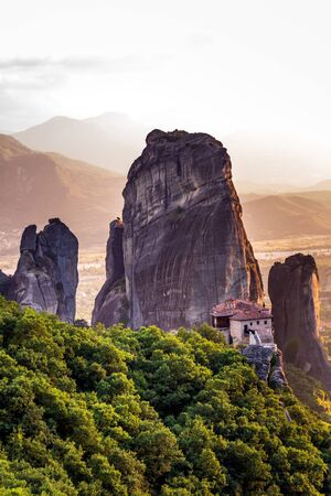 Monastery Meteora Greece. Stunning summer panoramic landscape. View at mountains and green forest against epic blue sky with clouds. Standard-Bild