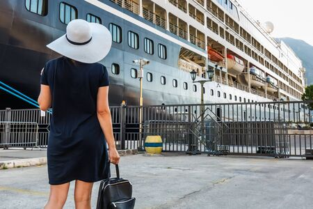 Happy lady in white hat and blue dress going on the cruise at Kotor, Montenegro. Rear view. Bay of Kotor bay is one of the most beautiful places on Adriatic Sea. Banque d'images