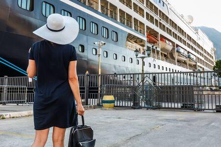 Señora feliz con sombrero blanco y vestido azul en el crucero en Kotor, Montenegro. Vista trasera. La bahía de Kotor es uno de los lugares más bellos del mar Adriático. Foto de archivo