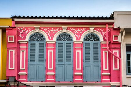 Wooden shutters on the windows in different shapes. Colorful buildings in old Phuket town in Thailand. Sino Portuguese style.