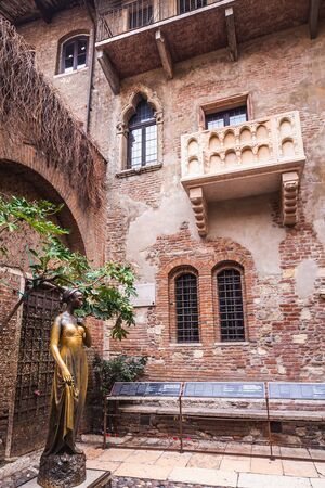 Patio and balcony of Romeo and Juliet house at golden sunset, Verona, Italy. Bronze statues of Juliet.