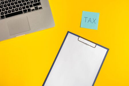 Flat lay out. Computer on yellow background with paper folio and blue note with reminder to pay taxes. Business concept idea. Copy space.