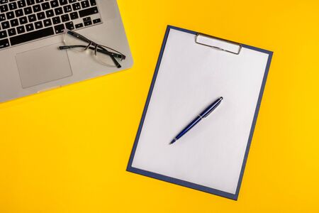 Flat lay out. Computer on yellow background with paper folio, pen and glasses. Business concept idea. Copy space.