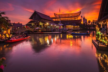 Sunset at famous Pattaya Floating Market which has traditional rowing boats. Villagers sell traditional foods and souvenirs. Foto de archivo