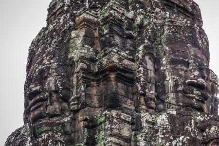 Ancient stone faces of Bayon temple. Old khmer temple ruins at Angkor Wat, Siem Reap, Cambodia. 版權商用圖片