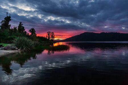 Lake Lanthe, Harihari, West Coast, New Zealand. Mirror lake landscape, beautiful sunset.