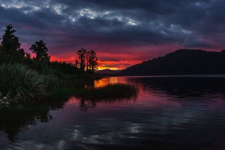 Lake Lanthe, Harihari, West Coast, New Zealand. Mirror lake landscape, beautiful sunset.