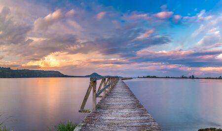 Vieux quai en bois tourné avec une longue exposition au coucher du soleil. L'emplacement est Tokaanu Wharf situé dans la région de Taupo de l'île du Nord, en Nouvelle-Zélande.