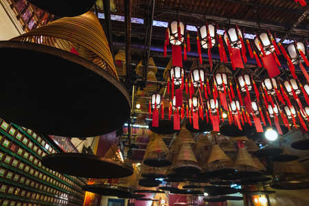 Interior of Man Mo Temple in Hong Kong with incense offerings and coils suspended from the ceiling at Hong Kong. Hong Kong. - April 03 2017.