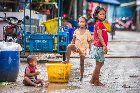 Lifestyle children in Thai countryside. Children playing water splash in street at countryside in Phuket, Thailand. Phuket, Thailand - March 28 2017. Éditoriale