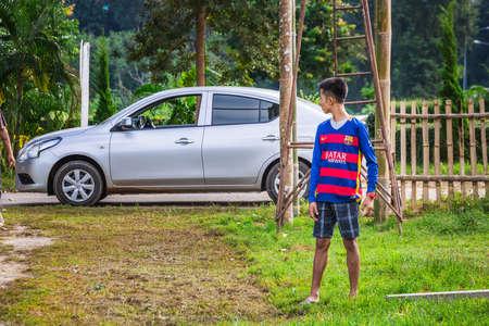 Local boy in the Barcelona football club t-shirt at the farm. Chiang Mai, Thailand - November 12 2017.