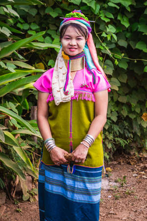 Long neck tribal woman stands in the jungle wearing traditional clothes and brass rings on her neck. Chiang Mai, Thailand - November 12 2017.