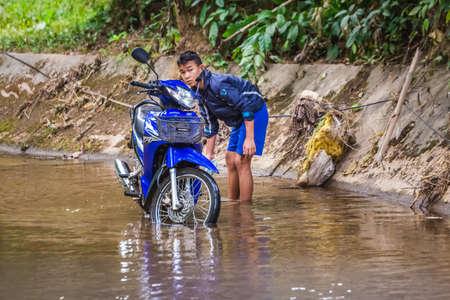 Tribal boy wash motocycle in the river. Chiang Mai, Thailand - November 12 2017. 2017.