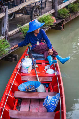 Old row man in blue hat and blue socks at famous Pattaya Floating Market which has traditional rowing boats. Villagers sell traditional foods and souvenirs. Pattaya, Thailand - November 17 2017.