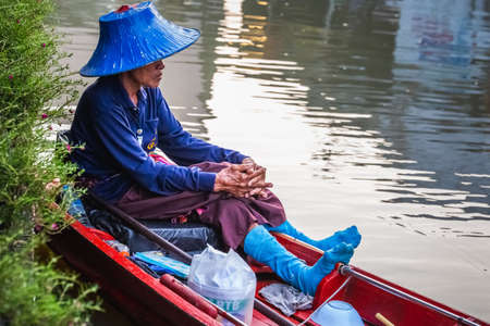 Old row man in blue hat and blue socks at famous Pattaya Floating Market which has traditional rowing boats. Villagers sell traditional foods and souvenirs. Pattaya, Thailand - November 17 2017. 免版税图像 - 151159439