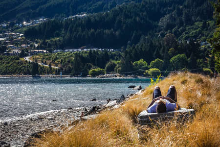 Man sleeping on a rock with book on his face at Queenstown New Zealand, South Island. Queenstown, New Zealand - December 18 2017.