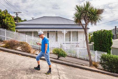 Man on the Baldwin Street - world s steepest street in Dunedin, Otago, New Zealand. Dunedin, New Zealand - December 20 2017.