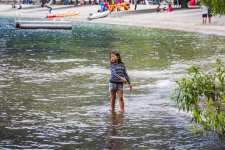 Young girl plays at the beach of Queenstown New Zealand, South Island. Queenstown, New Zealand - December 17 2017. Editorial