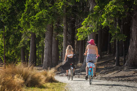 Young girls on a bicycles at Queenstown New Zealand, South Island. Queenstown, New Zealand - December 18 2017.