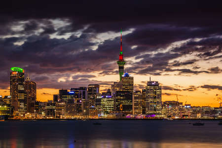 Auckland city skyline at sunset after heavy storm with city center and Auckland Sky Tower, the iconic landmark of Auckland, New Zealand. Auckland, New Zealand - December 17 2017.