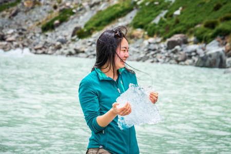 Asian girl hold peace of ice in the lake of Hooker Valley track at Mount Cook, New Zealand. Mount Cook, New Zealand - December 24 2017.