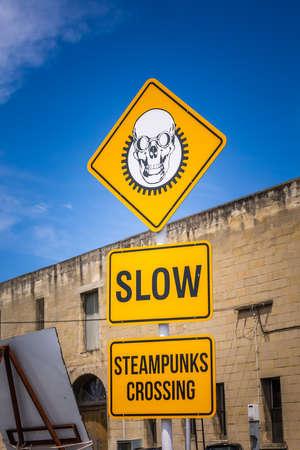 Steampunk yellow sign near SteamPunk Headquarter museum. Oamaru, New Zealand - January 07 2018.