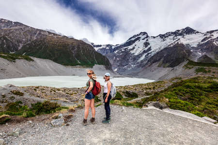 Couple of female tourists walking along the great winding track of Hooker Valley at Mount Cook, New Zealand. Mount Cook, New Zealand - December 24 2017.