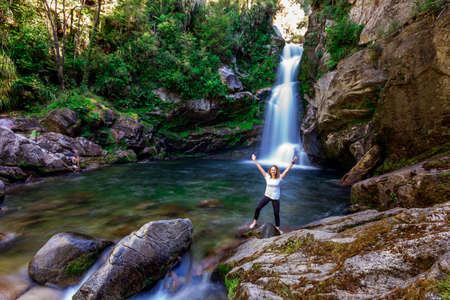 Girl in a water with waterfall in the background after hiking a trail. Abel Tasman National Park, New Zealand - December 30 2017.